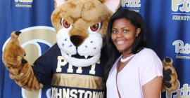 student standing next to Pitt Johnstown mascot