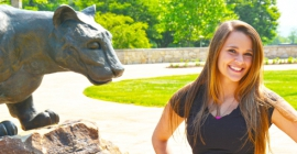 Student posing in front of Mountain Cat statue