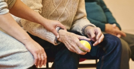 Elderly person holding a ball