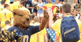 student high-fiving Pitt's mascot