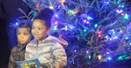 children standing next to Christmas tree