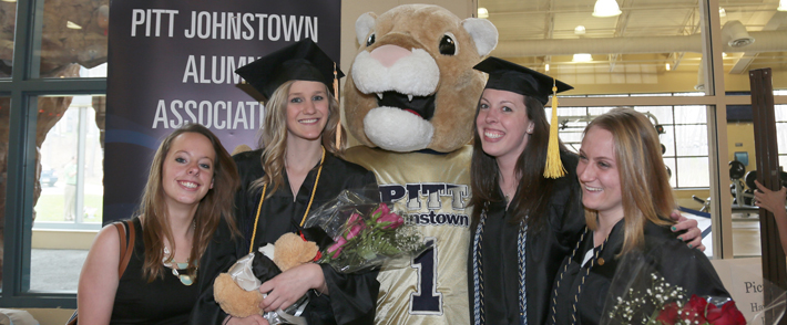 graduates standing with mascot